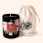a candle in a black jar decorated with floral illustrations alongside a cotton storage bag decorated with a printed flower drawing
