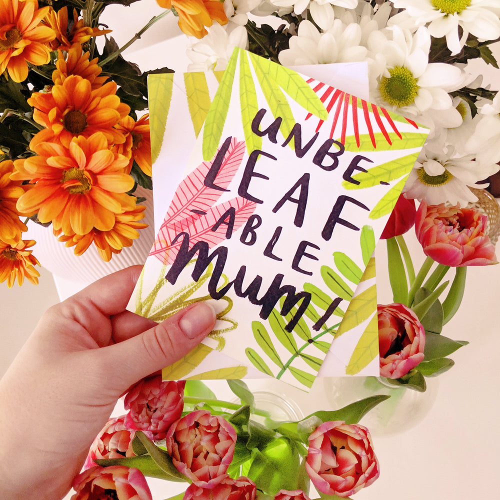 mother's day card help up against bunches of flowers