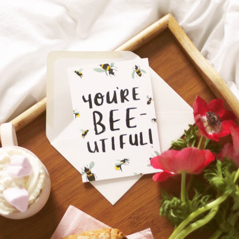 You're Bee-utiful Card, resting on a breakfast in bed tray surrounded by frothy coffee and flowers