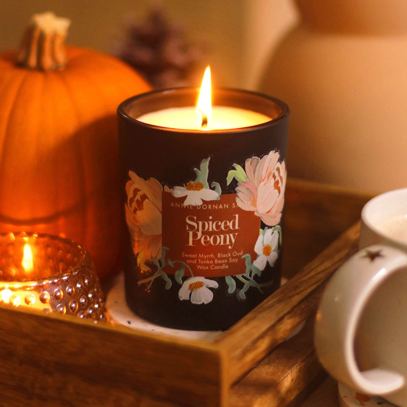 A black candle with a floral label, burning on a wooden tray of candles and autumn decor