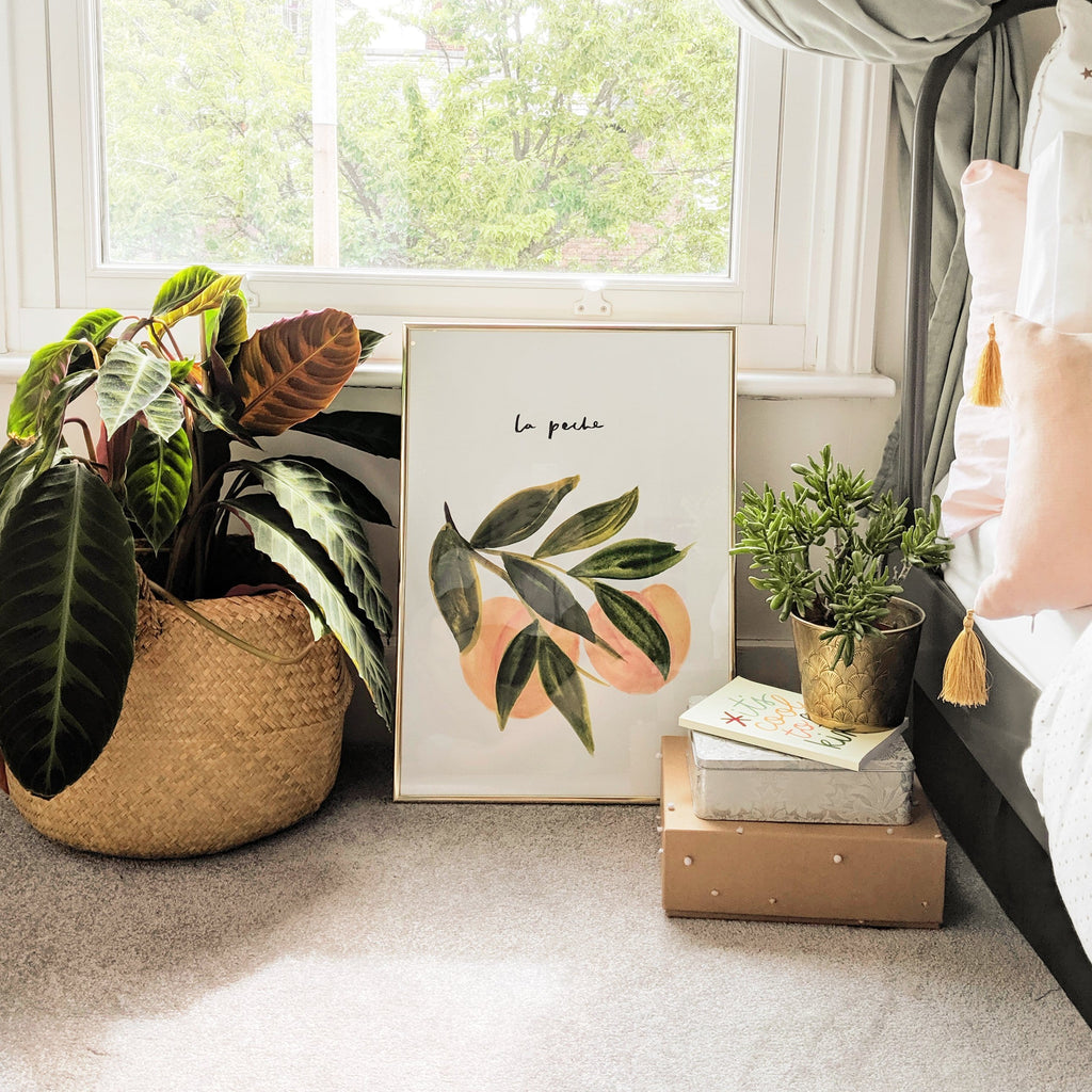 The la Peche Print in a gold frame, propped up next to a bed and a green leafy houseplant