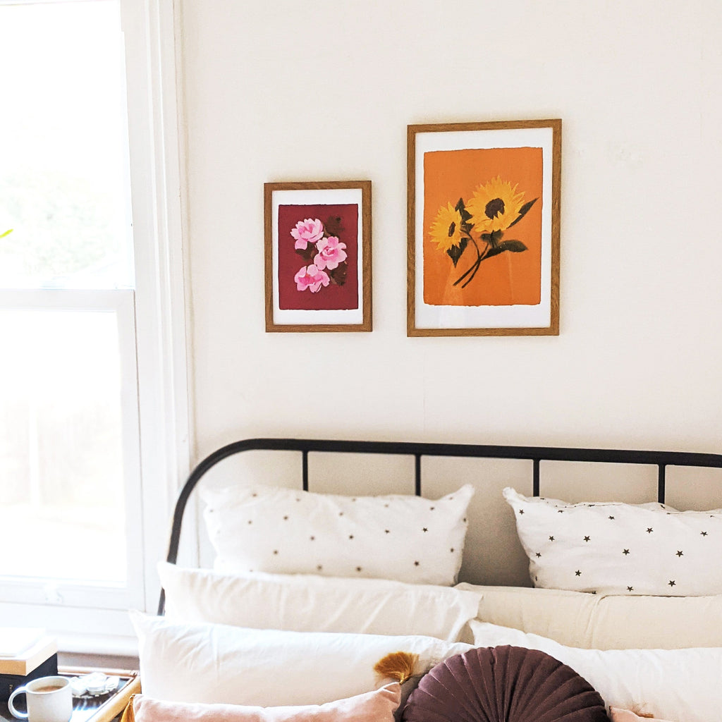 a light and airy bedroom with a cup of coffee on the nighstand. Two flroals printsh ang above the bed.