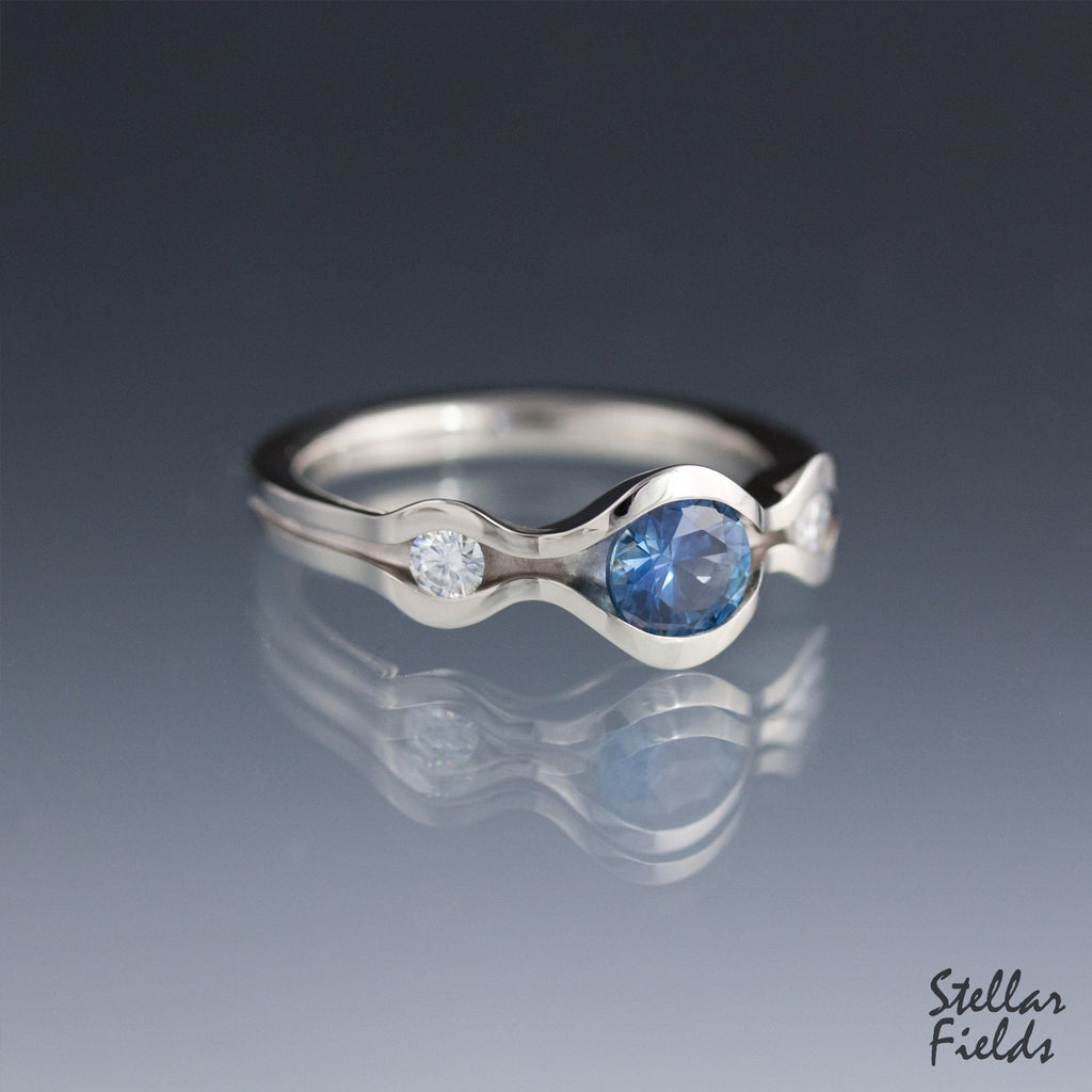 blue montana sapphire three stone engagement ring with diamond accents modern wave design stellar fields jewelry