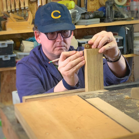 Charles, instructor in a woodshop, makes a mark on lumber