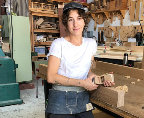 Sarah stands in a woodshop holding a hand plane.