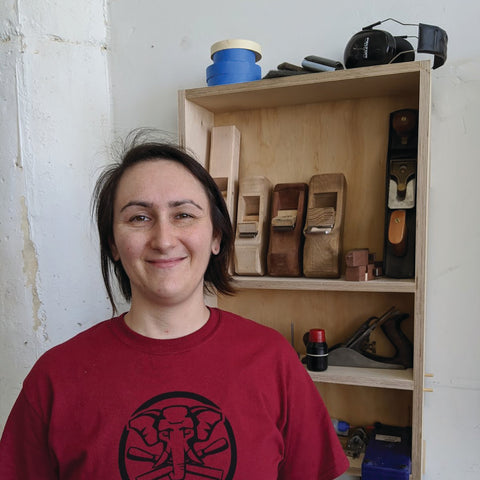 Shay Voyager stands in front of a wall hung cabinet displaying hand planes and other tools