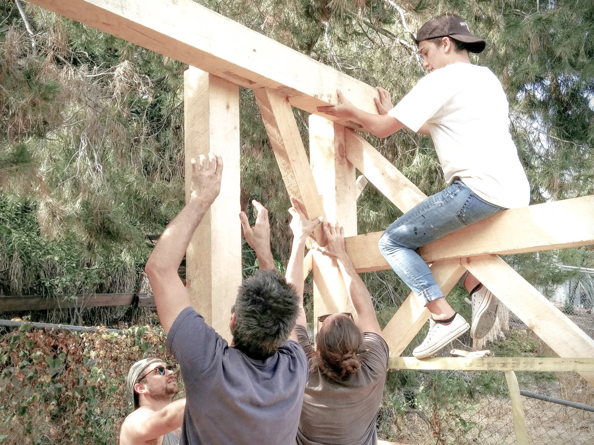 Woodworkers work together to erect and assemble large wooden beams
