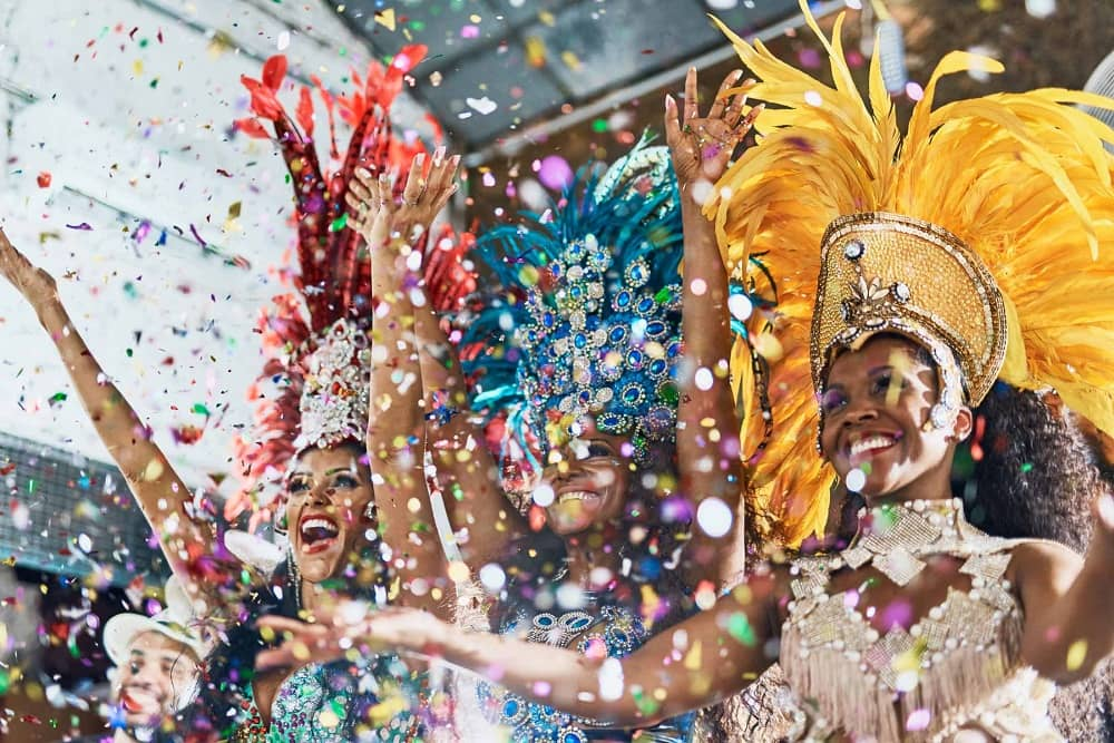 Notting Hill Carnival 2019 - women in colourful carnival costumes with confetti
