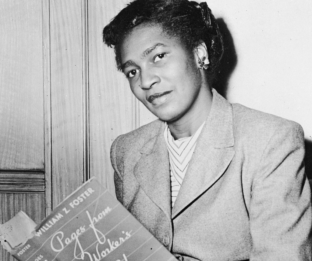 Black and white photograph of Claudia Jones reading a newspaper