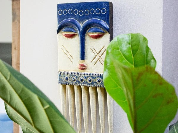 Comb mask hung on a wall behind a plant