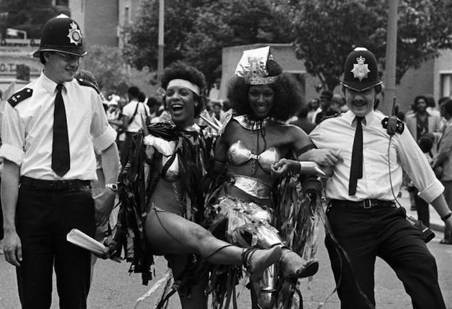 Notting Hill Carnival - black and white photo showing carnival dancers linking arms with police men