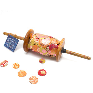 Wooden spool hand made using recycled paper in India with 25 meters of metallic copper, orange, yellow and pink spotty garland for birthdays, parties and wedding decoration.