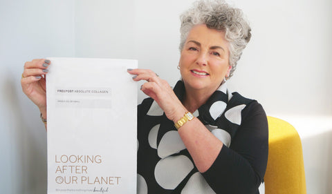 Photo of a white woman with short grey hair smiling at the camera and holding up a white plastic mailing bag.