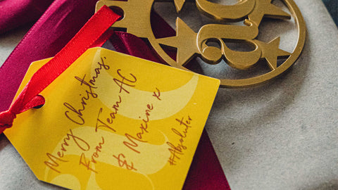 Close up photo of a gold Absolute Collagen Christmas decoration and bright yellow gift tag from Maxine