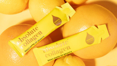 Photo showing two Absolute Collagen sachets lying on a pile of oranges