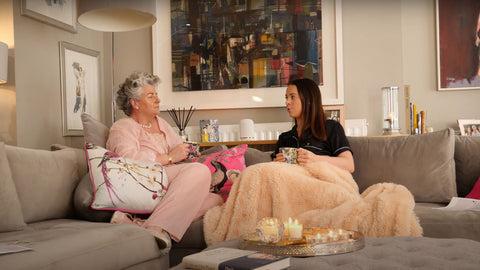 Photo of Maxine and Margot Laceby wearing pyjamas and sitting under a blanket together on their settee, the lighting is soft and they are chatting to each other