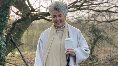 Photo showing Maxine Laceby smiling and standing outside by a tree, she is holding a reusable coffee cup and wearing a light cream coat