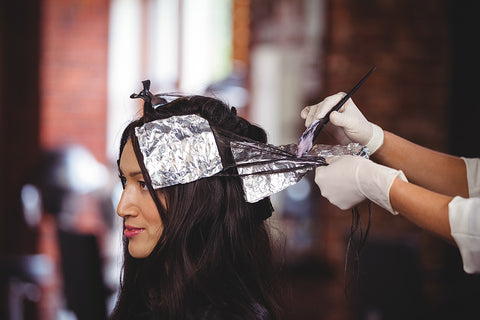 Photo showing a white woman with brunette hair facing left and having silver foils applied by a hairdresser