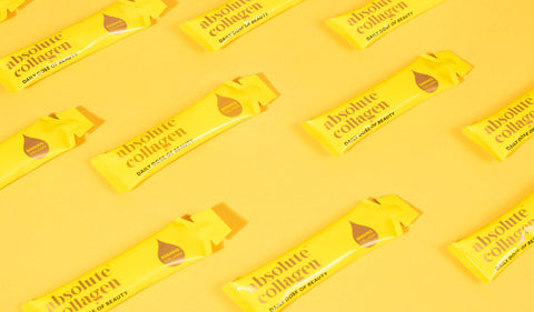 Several yellow Absolute Collagen sachets laying on a yellow background