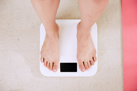 Image of a white woman's feet on bathroom scales as she weighs herself