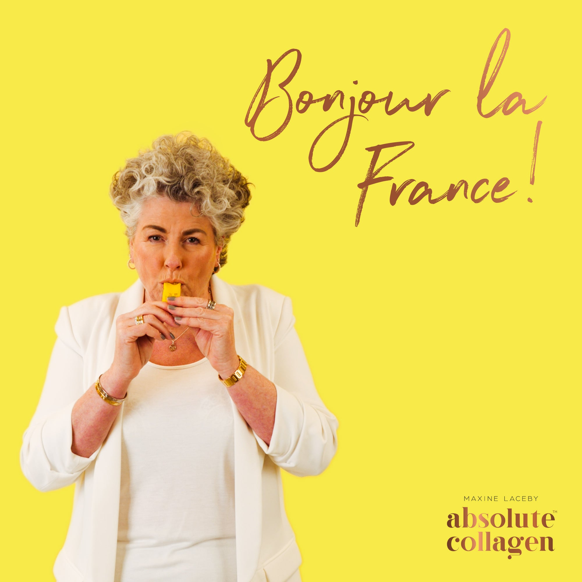 Photo showing Maxine Laceby wearing white and standing against a yellow background, she is taking a sachet of Absolute Collagen and the words Binjiur la France are emblazoned in copper writing to her right