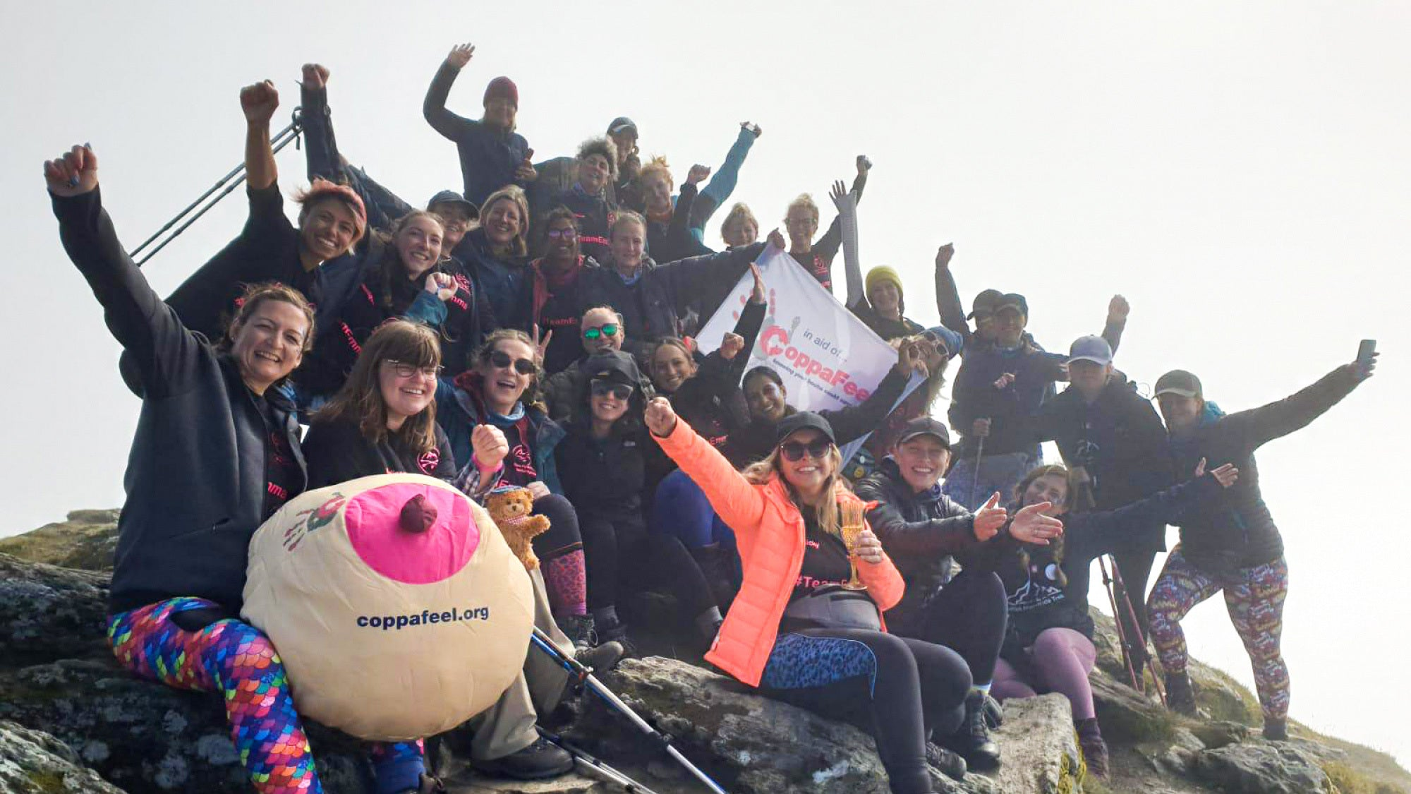 Photo showing a group of hikers holding their arms aloft while sat on a mountain top.