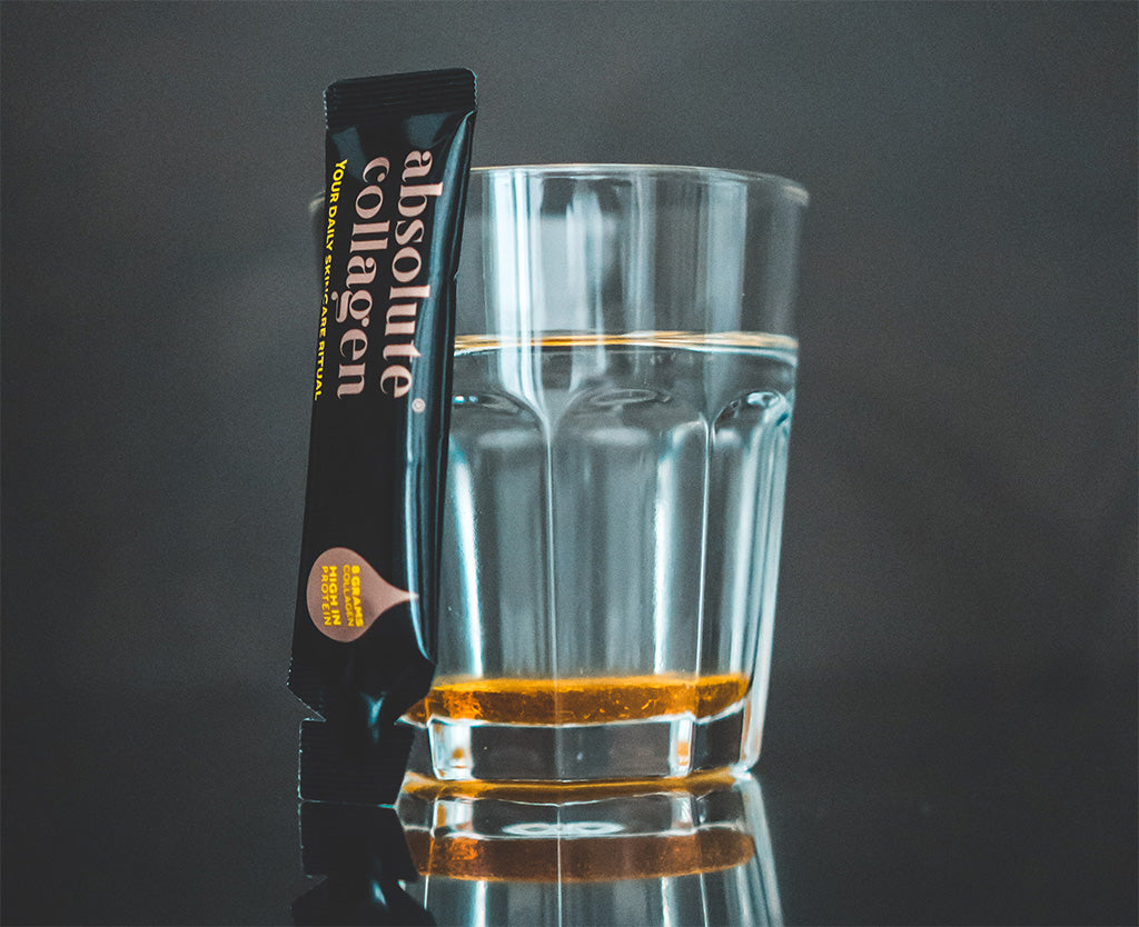 Photo showing a glass of water next to a black Absolute Collagen sachet, both standing against a dark grey background