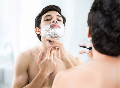 Man shaving and seeing reflection in mirror.
