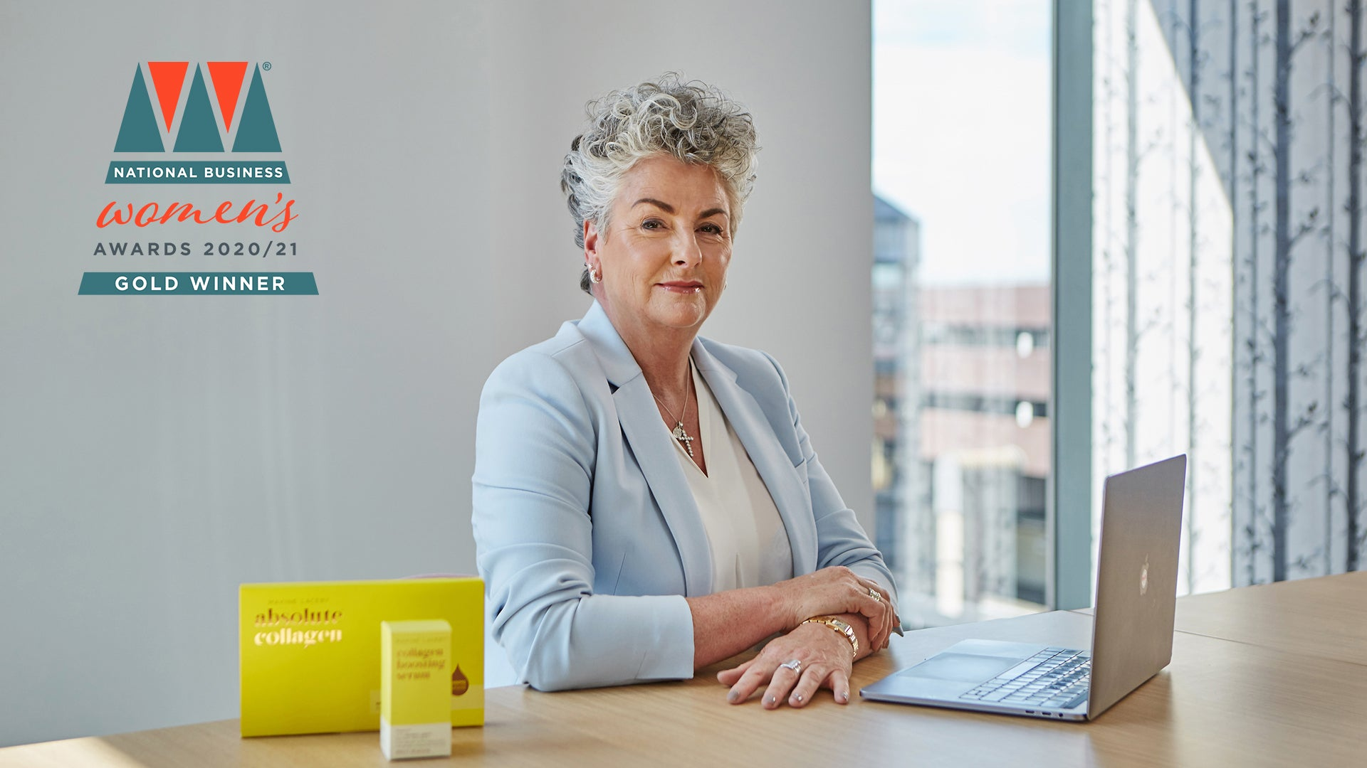 Photo showing Maxine Laceby wearing a pale blue blazer and sitting at a desk, she is looking at the camera and the National Business Woman Gold Winner logo is superimposed on the image to the left of her