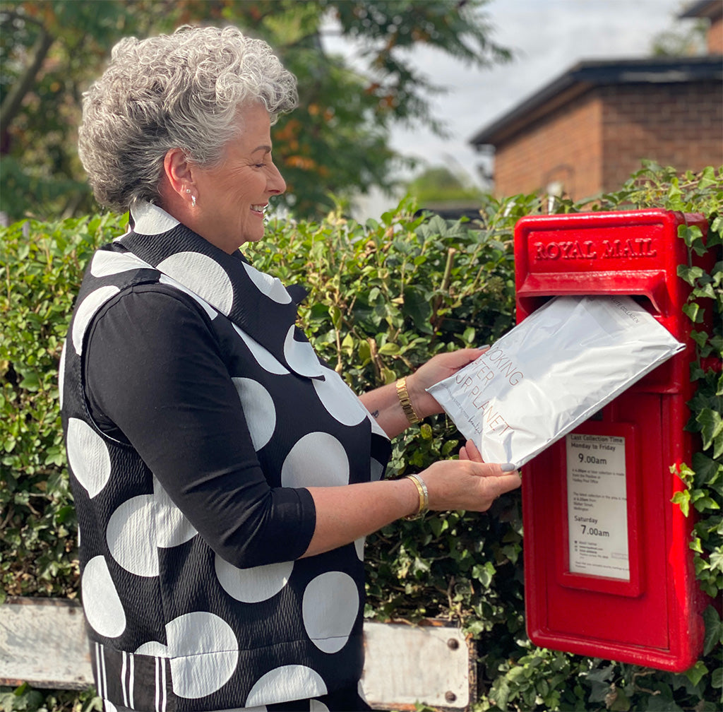 Photo showing a short haired white woman wearing a black and white spotted top andposting a white envelope into a postbox
