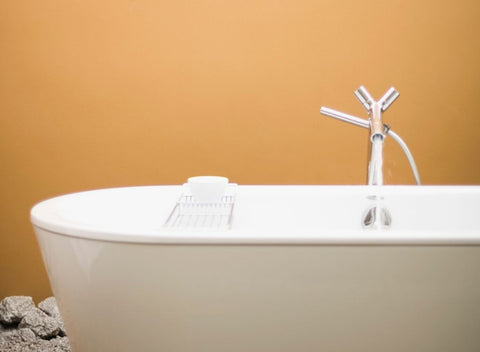 White bathtub on orange background.