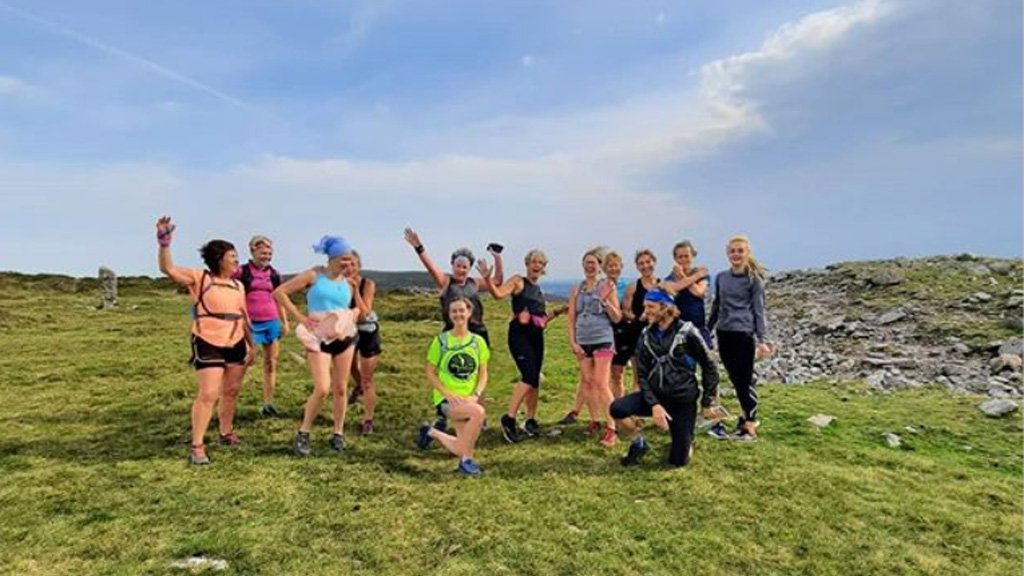 Photo showing a group of women in colourful running gear standing on a hill against a blue sky while a man crouches in front of them