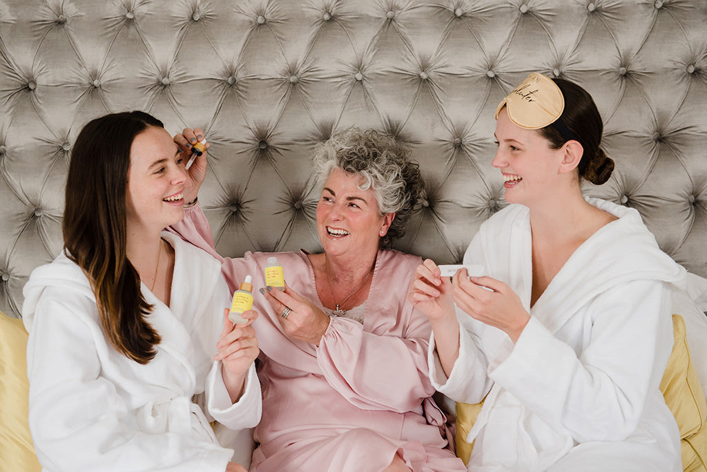 Photo showing two brunette white young women sat either side of a white woman with grey hair, all three are wearing dressing gowns and laughing together against a grey bed headboard while holding bottles of Maxerum