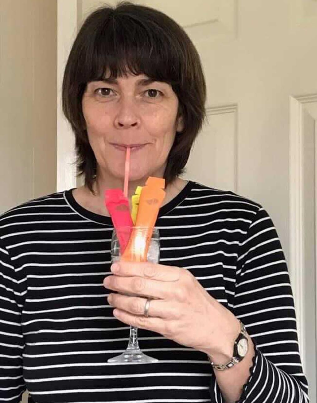 Photo of a white woman with chin length dark hair, she is wearing a black and white striped top and holding up a cocktail glass of Absolute Collagen sachets and playfully miming drinking them through a straw