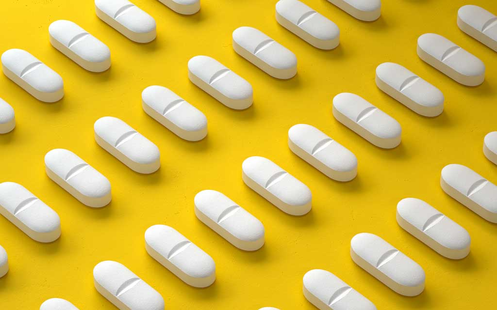 Pills lined up containing collagen supplements, on a yellow background.