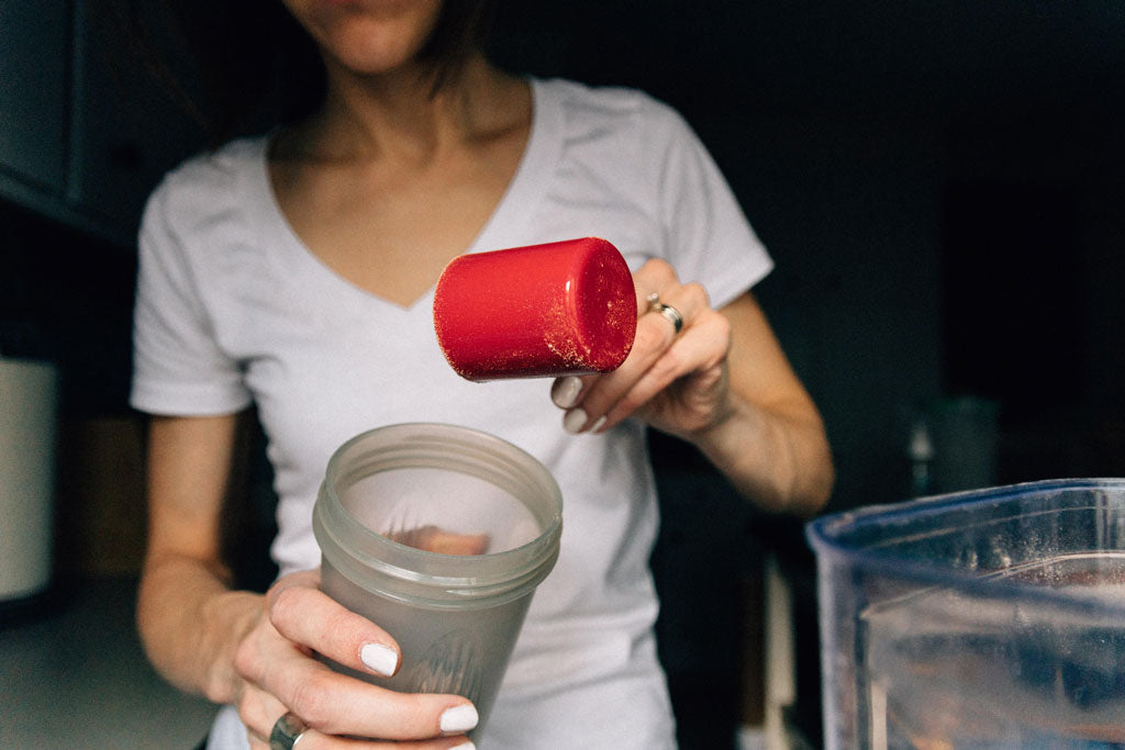 Woman pouring collagen powder into a drink.