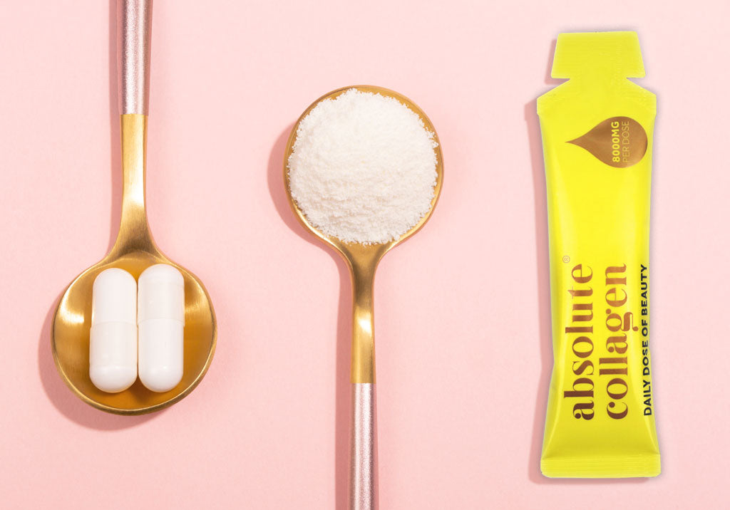 Two teaspoons containing collagen powder and collagen pills, on a pink background.