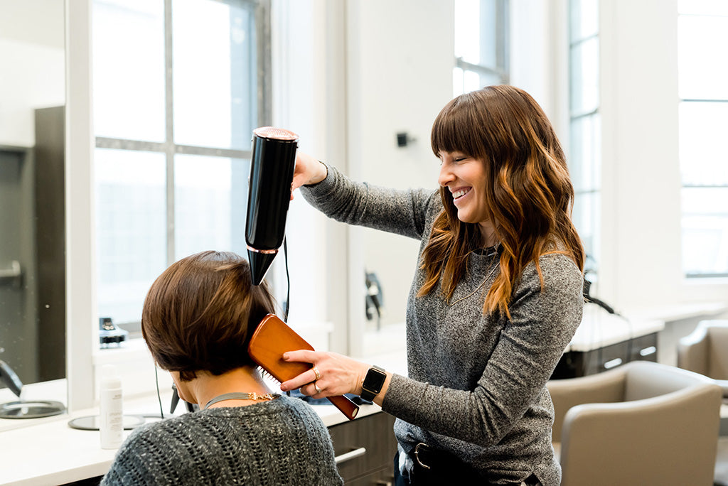 Photograph of a white woman holding a hairdryer and laughing with a hairdressing client sat in a chair with their back to the camera