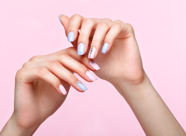Pink and purple manicured nails on pink background, showing collagen for nail growth