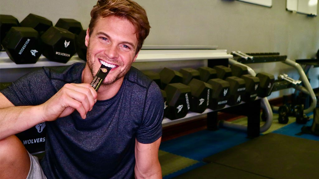 Photo showing a smiling white man in activewear, he is sitting in a gym and taking an Absolute Collagen sachet