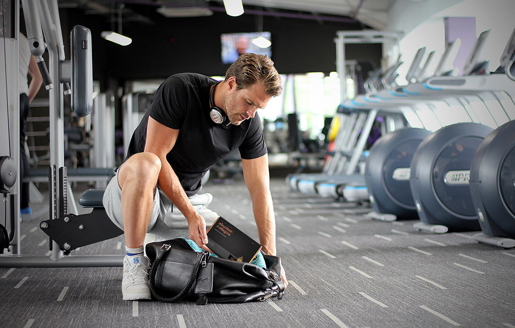 Photo of a fair-haired man kneeling down in a gym and reaching into a sports bag