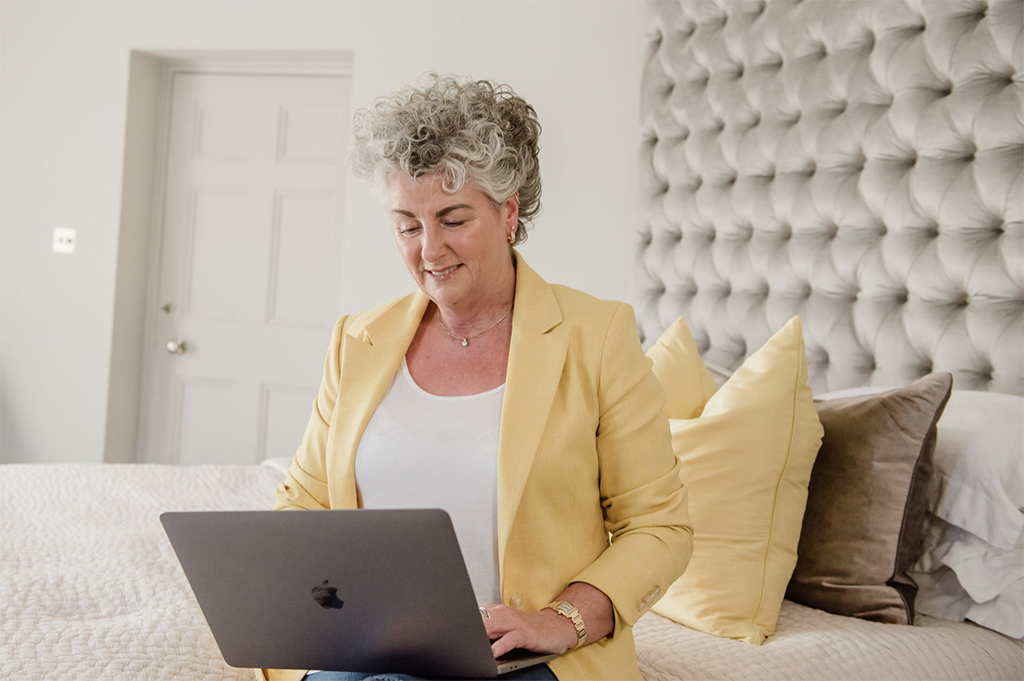 Maxine Laceby wearing a yellow blazer and sat on a bed working on a laptop