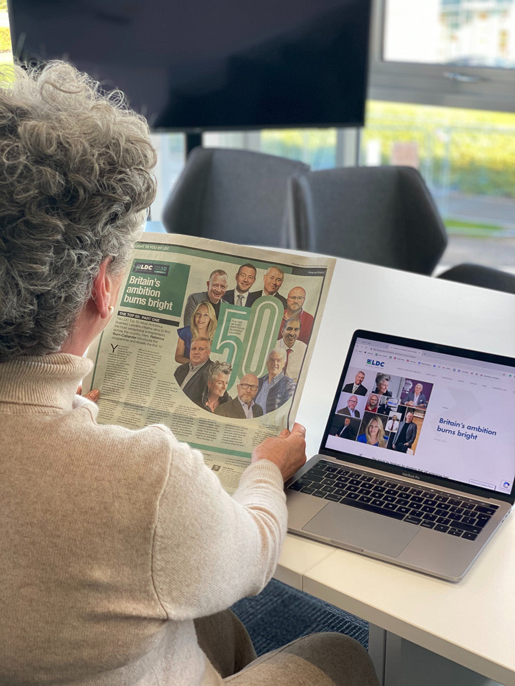 Photo showing a white woman with short silver hair sat at a laptop and holding a newspaper with her back to the camera