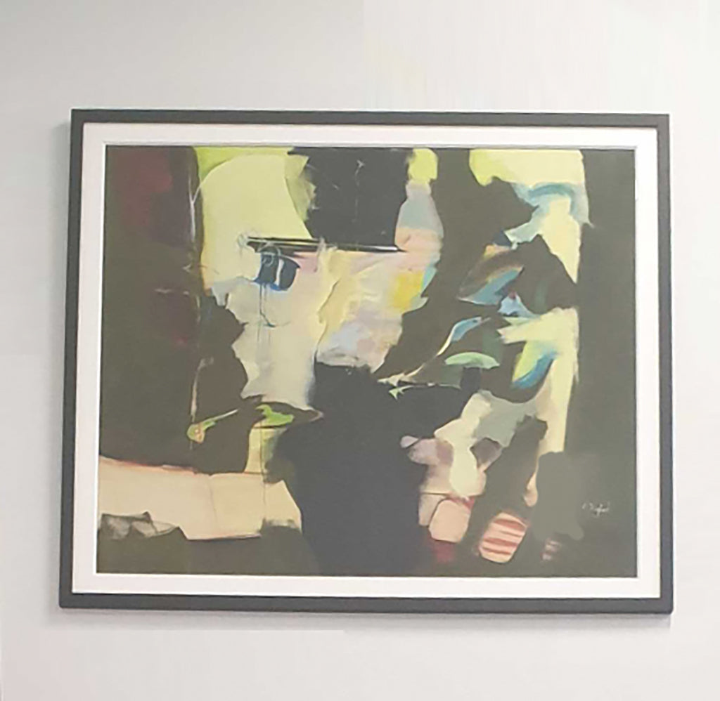 Photo of an abstract art piece in black and yellow, hanging on a white wall