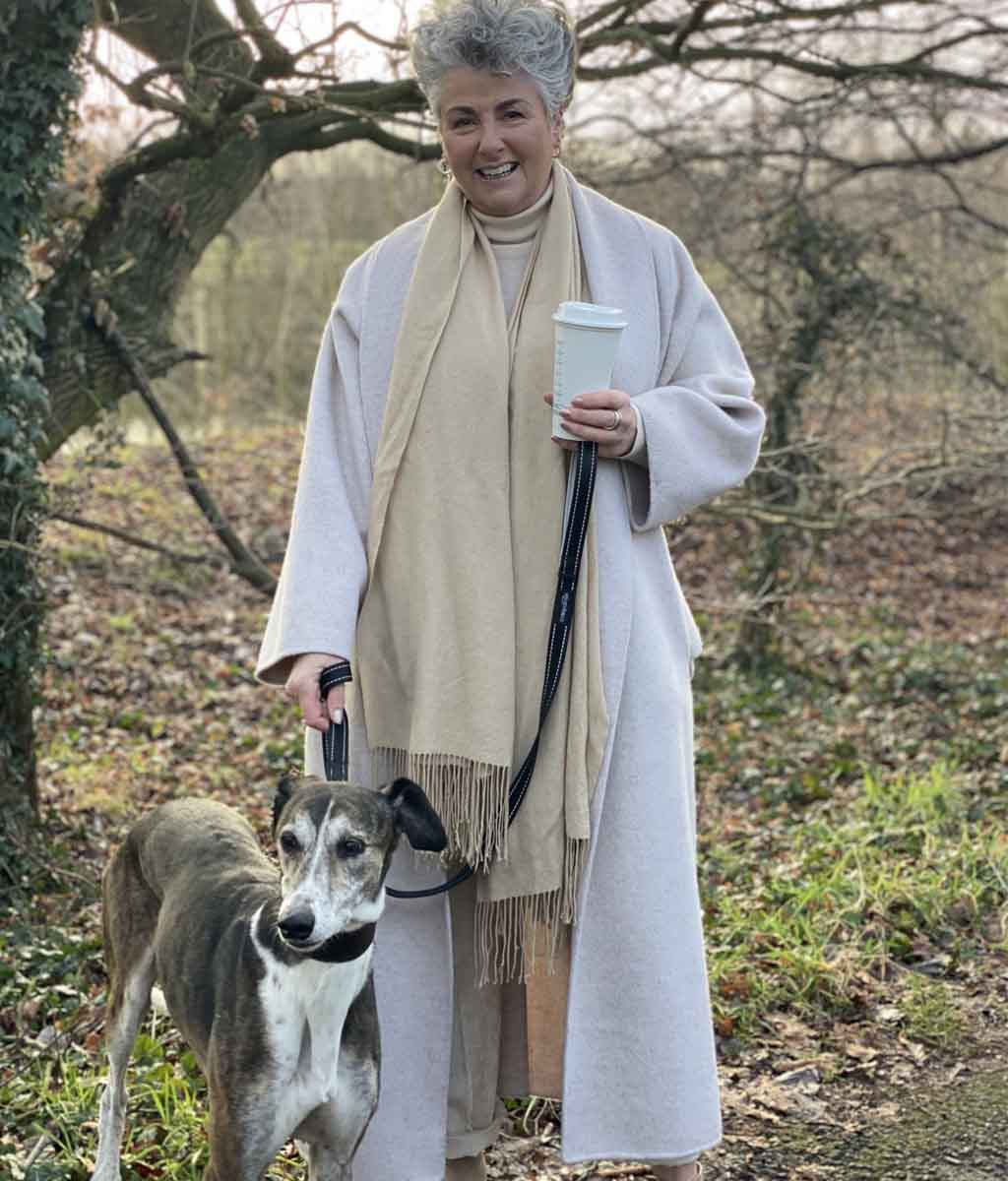 Photo showing Maxine Laceby standing outside by a tree, she is smiling and wearing a long cream coat and holding a reusable coffee cup, and her lurcher Rosie is standing by her