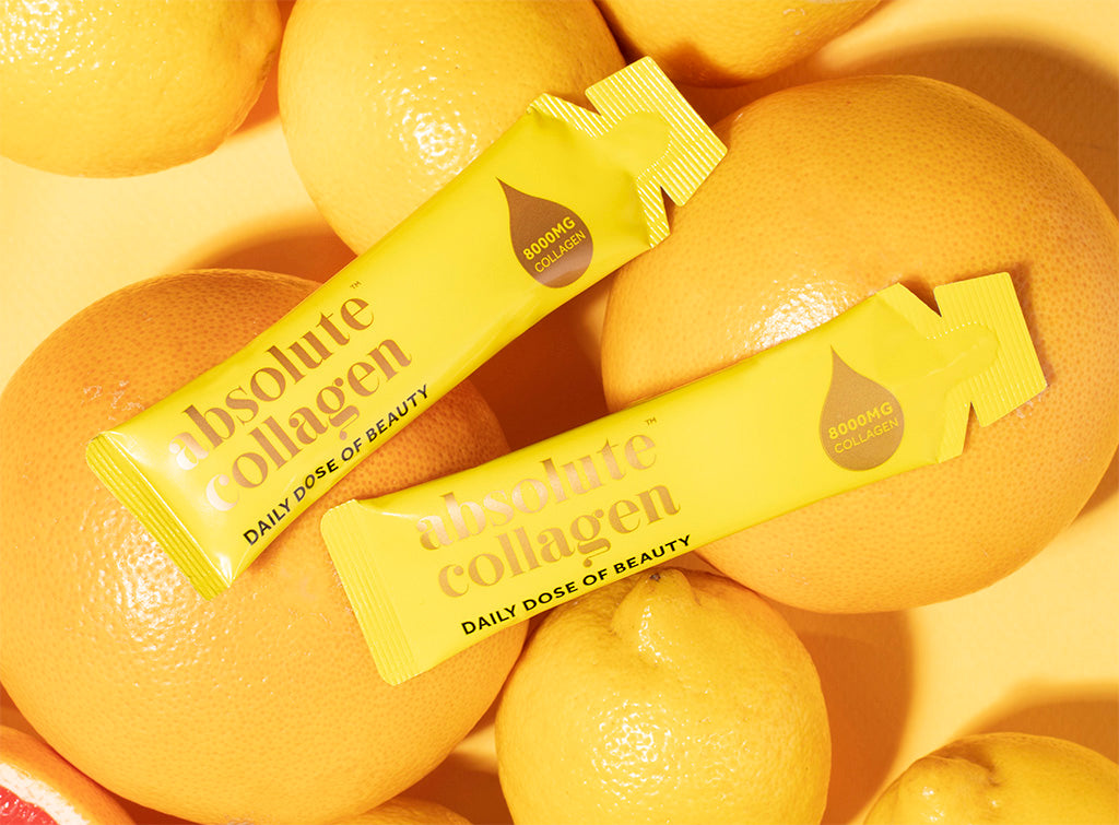 Photo of yellow Absolute Collagen sachets with oranges and lemons in the background