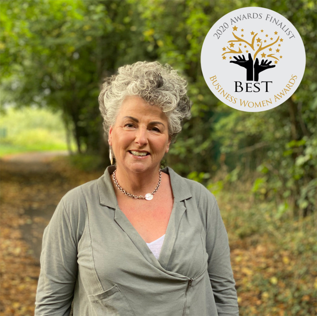 Photo showing a white woman with short wavy silver hair and wearing a grey top smiling at the camera against a forest background, with a roundel listing her as a Best Businesswoman Awards finalist in the upper left corner of the image