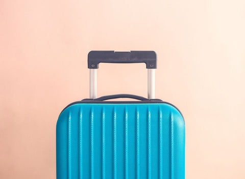 Blue suitcase on pink background. Book a getaway to beat Blue Monday & the January blues - Absolute Collagen