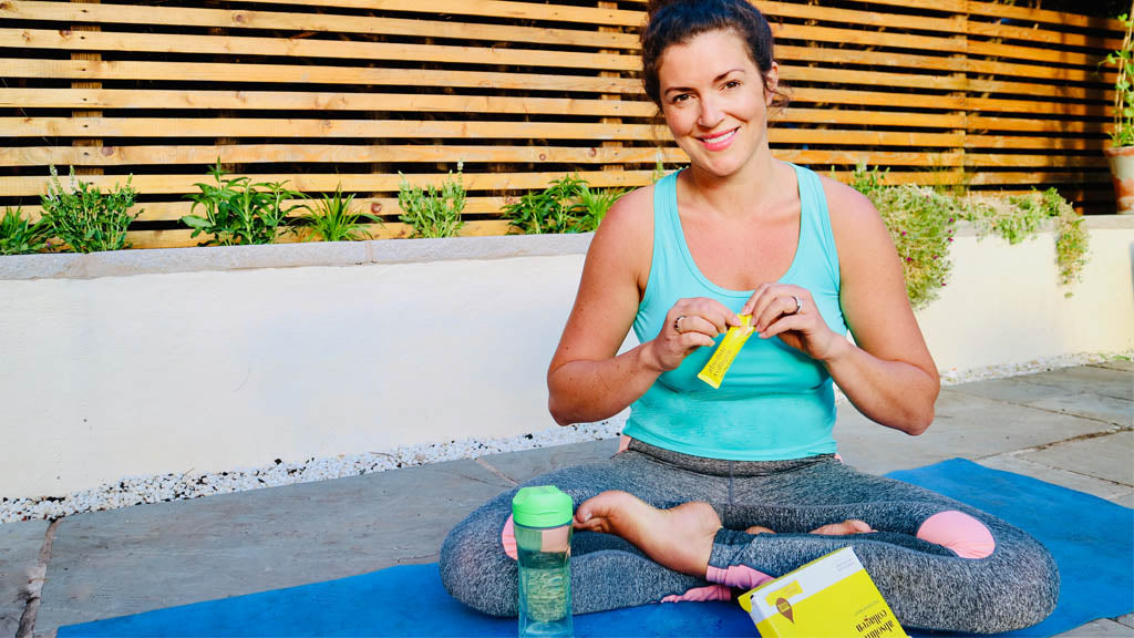 Photo of a brunette white woman wearing a bright blue vest top and grey leggings sitting on a yoga mat, she is smiling and holding an Absolute Collagen sachet with an Absolute Collagen box in front of her