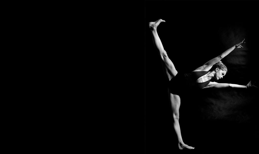 Charlotte Tooth dancer stretching on black background